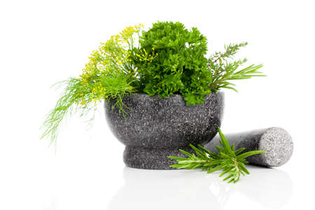 Stone mortar with green herbs, on white background photo
