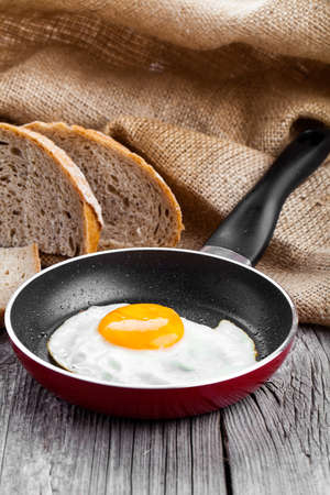 Fried egg in a frying pan, on an old wooden table photo