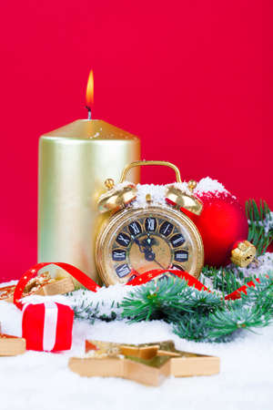 pine branch: Christmas decorations - clock for the new year, candle, pine branch on orange background Stock Photo