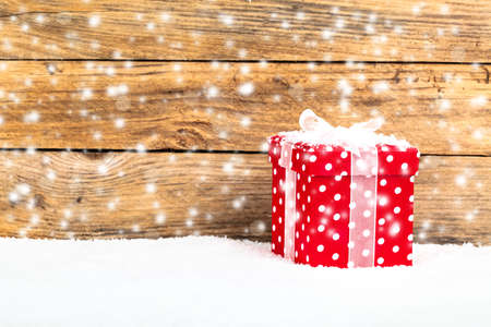 red gift for christmas on a wooden background with snow photo