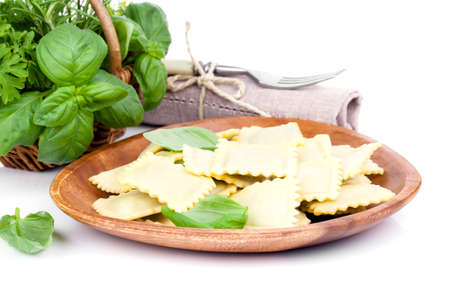 homemade style: Homemade pasta ravioli with fresh basil, isolated over white background.