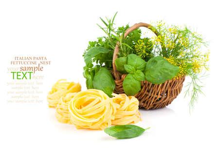 Italian pasta fettuccine nest with wicker basket green herbs, on white background photo