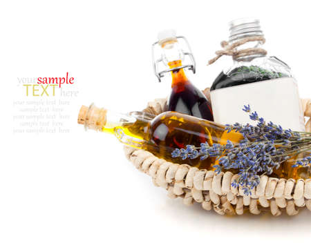 Essential various oils with lavender flowers, on white background. Banque d'images