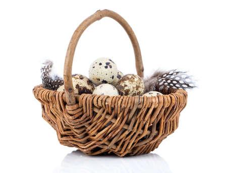 Huevos de codorniz en una cesta de mimbre en el fondo blanco Foto de archivo - 38450154