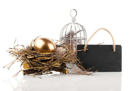 golden egg in nest with blackboard with space for text, on white background photo