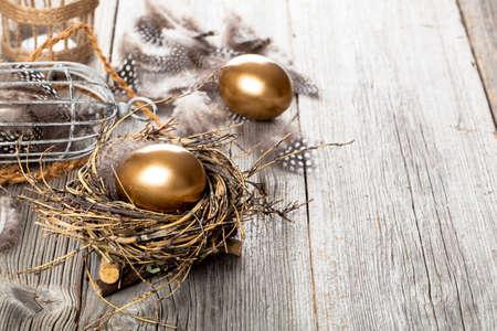 golden egg: golden egg in nest, on wooden background