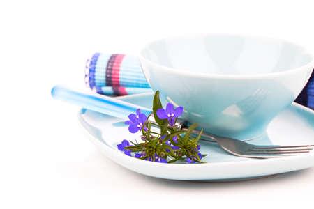 lobelia: tableware with blue lobelia flowers and cutlery, on a white background.
