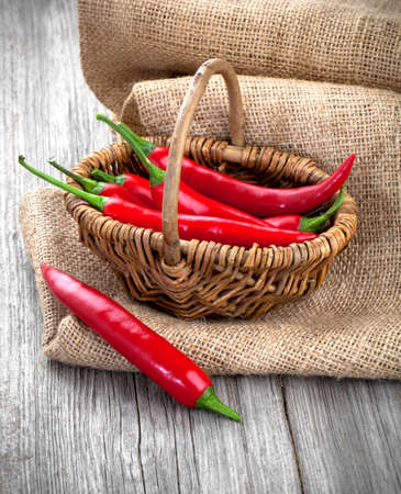 red pepper: Red chili pepper in a wicker basket with burlap on the wooden background