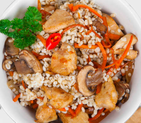 Barley porridge with, meat, mushrooms and carrots Stock Photo