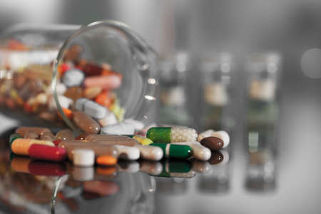antibiotic pink pill: Colorful tablets with capsules and pills on background