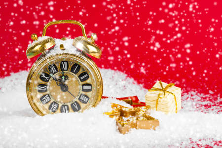 five to twelve: vintage christmas decoration golden star and antique golden clock in snow on red background Stock Photo