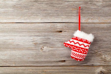 christamas: Red mitten on wooden background