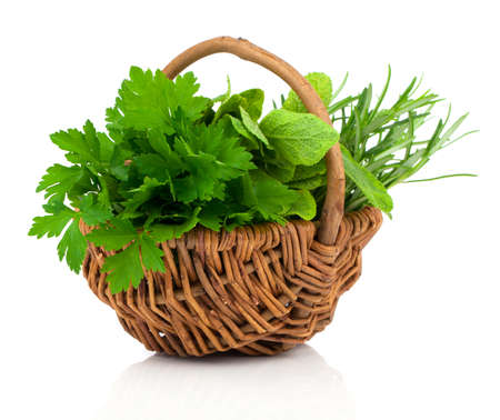 wooden basket: sage, parsley and rosemary in wicker basket, on a white background