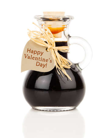 ardent: maple syrup in glass bottle or herbal syrup, ardent drink, mixture, with heart label. on white background.