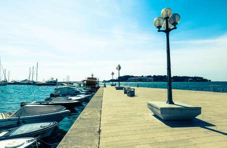 berth: wooden berth with street-lamp on sea background. Pula Croatia Stock Photo