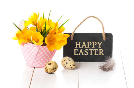 pascuas navideÑas: easter decoration with quail eggs, yellow Spring Crocus, and blackboard, with space for text, on wooden white background.