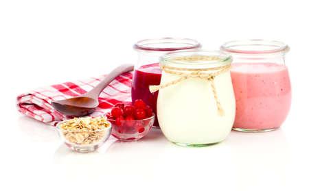 yogurt natural: yogur deliciosa, nutritiva y saludable en unos frascos de vidrio con cuchara sobre un fondo blanco
