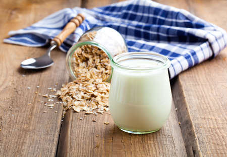 glass jars: Delicious, nutritious and healthy yogurt in a glass jars with spoon on wooden background Stock Photo