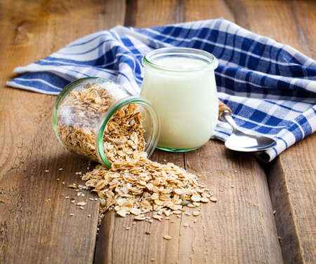 oats: Healthy yougurt with oat flakes, in a glass jars on wooden background Stock Photo
