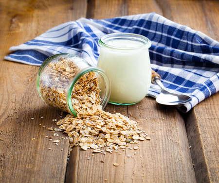 avena: yogur sano con los copos de avena, en unos frascos de vidrio sobre fondo de madera