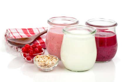 白い背景にスプーンとガラス瓶の中でおいしい、栄養価の高い健康的なヨーグルト