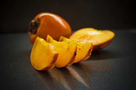 Slices full and half of diospyros kaki on a dark background. Persimmon fruit, selective focus