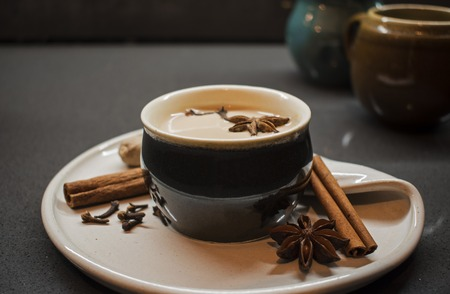 Indian tradition milk drink, masala chai tea with spices. Cinnamon Stick, Clove, Star Anise, Nutmeg and dark brown cup on ceramic plate, stone background