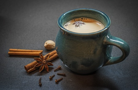 Indian tradition milk drink, masala chai tea with spices. Cinnamon Stick, Clove, Star Anise, Nutmeg and turquoise ceramic cup on dark background