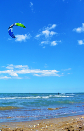 Lido di Classe, Italy - July 4, 2017: Young Man ride Kite Surf, Fun in the sea, Extreme Sport Kitesurfing or kiteboarding