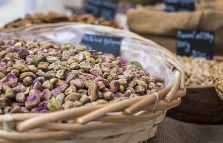 Background of basket of pistachios without shells, captured on street market, selective focus