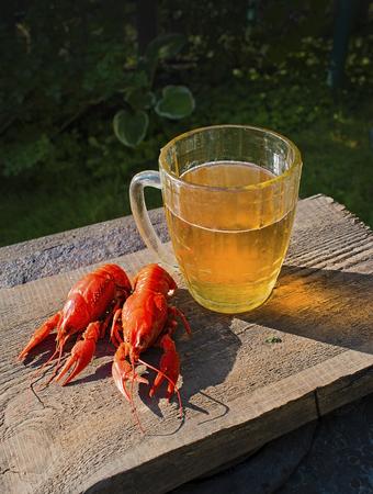 Glass of beer on a old wooden desk. Boiled crayfishes. Summer garden atmosphere.