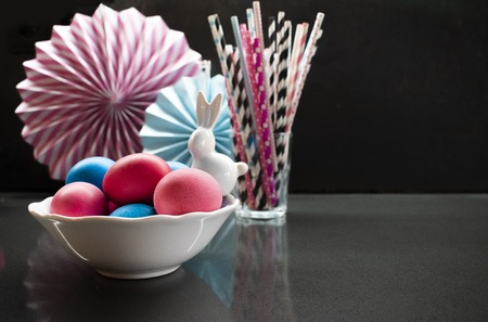 Easter holiday creative  with eggs, porcelain bunny and paper decoration. White, pink, blue color on dark.