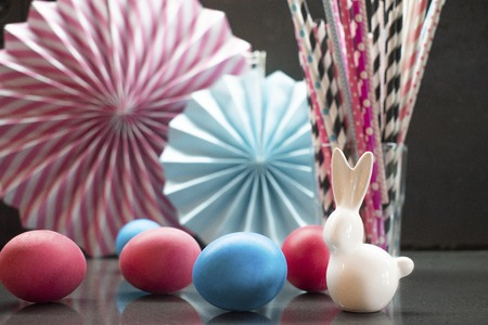 Easter holiday background with eggs, porcelain bunny and paper decoration