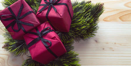 red gifts decorated with fir tree branches on wooden background