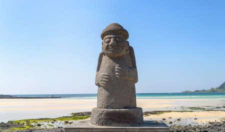JEJU-EILAND, ZUID-KOREA, 10 SEPTEMBER, 2015: standbeeld van Dol hareubang - symbool van Jeju-eiland op zonnige dag met overzees en strand op achtergrond