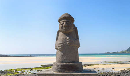 JEJU ISLAND, SOUTH KOREA, SEPTEMBER 10, 2015: statue of Dol hareubang - symbol of Jeju island on sunny day with sea and beach on background Редакционное