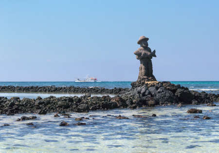 JEJU ISLAND, SOUTH KOREA, SEPTEMBER 10, 2015: statue of fisherman made of lava rock in the sea Editorial