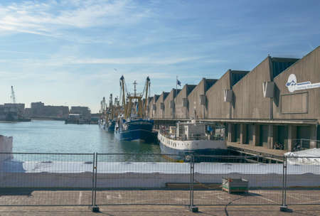 Hague, The Netherlands, October 05, 2018: Fish Auction Scheveningen B.V. and fishing vessels on sunny day