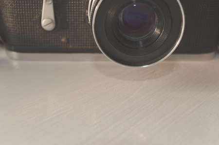 Part of old camera and lenses on wooden table in sunlight Banco de Imagens