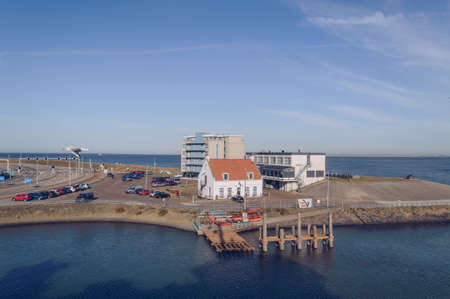 Den Helder, The Netherlands, October 13, 2018: view from ferry on Hotel Lands End and Pepper house with parking lot and coastline