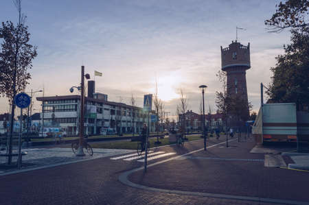 Den Helder, The Netherlands, October 13, 2018: view of citizen of Den Helder riding bicycles in the evening with Water tower Redactioneel