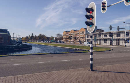 Close up view of traffic lights and canal in cityscape of Den Helder