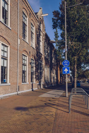 Brick houses and pavement sidewalk with parking for bicycles on sunny october morning in Den Helder Stockfoto