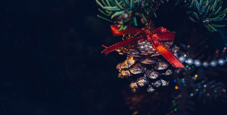 golden pine cone with red bow and dark background with space for text Banco de Imagens