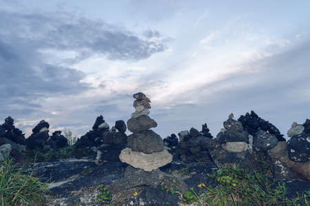 close up view of one of the happiness pyramid  made of jeju lava rocks on one of the Jjeu island beaches Banco de Imagens