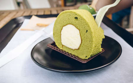 close up view of fresh green tea roll cake being eaten