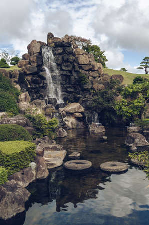 Jeju Island, South Korea, september 05, 2019: Beautiful landscaping of waterfall and pond inside of Spirited garden on cloudy day