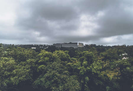 landscape of buildings, green trees in forest and gloomy skies over it