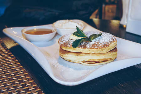 fluffy pancakes with maple syrup served on white plate and decorated with mint leaf