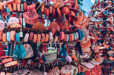 Busan, South Korea, September 14, 2019: close up view of heart shaped locks with wishes and names on tags near Busan tower